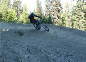 A rider rides a dirt burm along one of the free ride downhill trails.